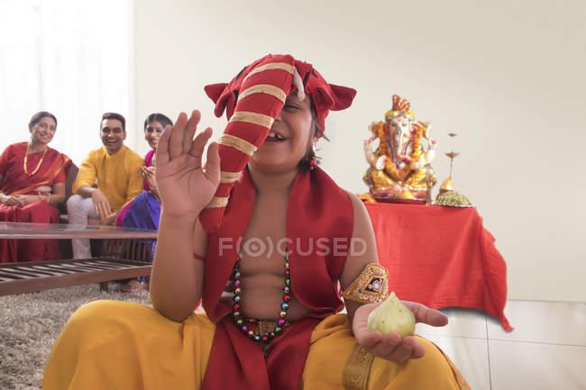 Enfant assis habillé comme Roland avec modak dans une main et Roland idole en arrière-plan — Photo de stock