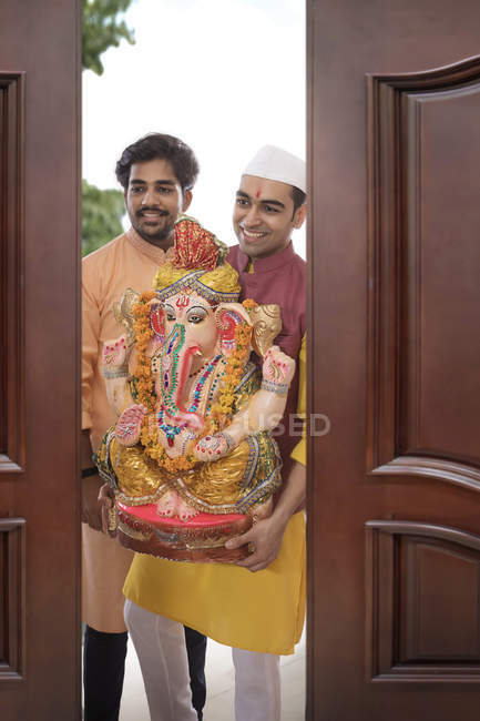 Dos hombres indios en ropas festivas con estatua religiosa en manos - foto de stock