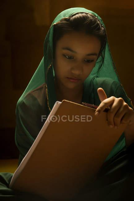 Ritratto di ragazza indiana guardando pad esame sotto la luce posteriore — Foto stock