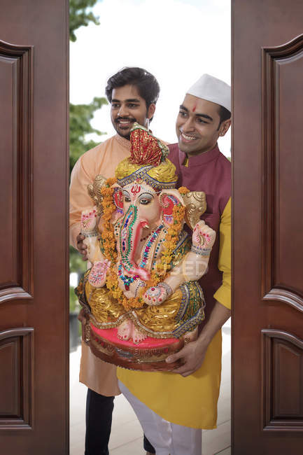 Two indian men in festive clothes with religious statue in hands — Stock Photo