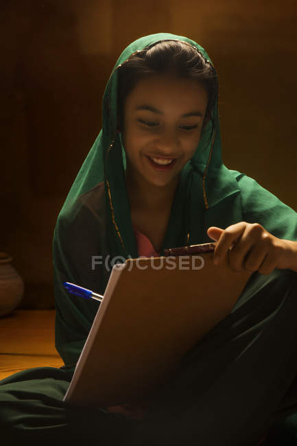 Portrait of Indian girl looking at exam pad under back light — Stock Photo