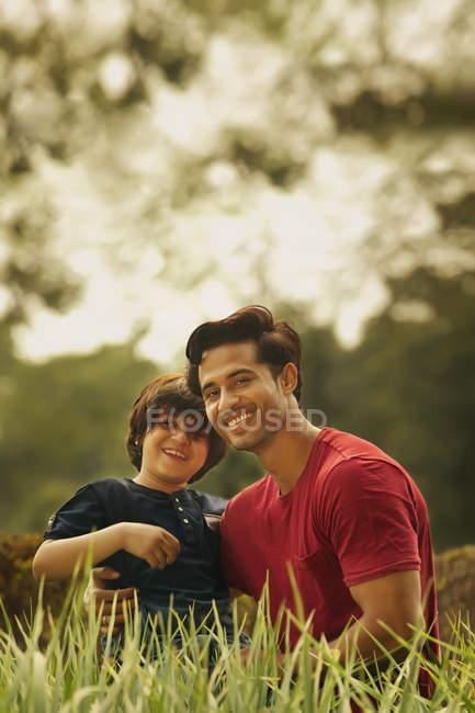 Sorrindo pai e filho sentado na grama no parque — Fotografia de Stock