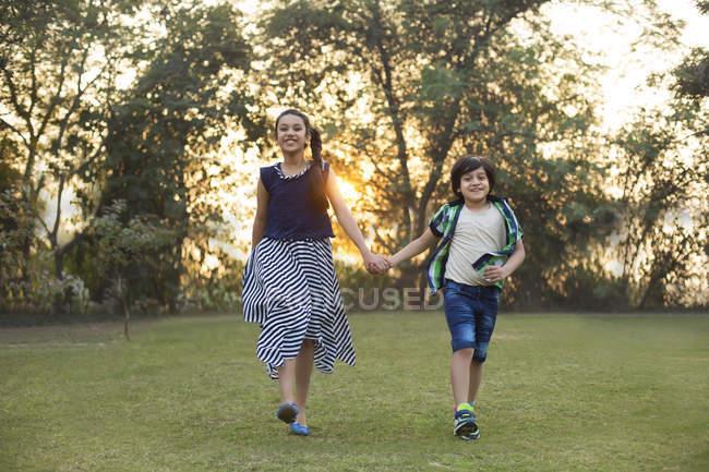 Feliz irmão e irmã, quando andando no parque de mãos dadas — Fotografia de Stock