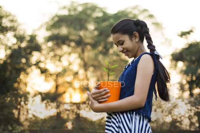 Vista a basso angolo di sorridente ragazza che tiene il vaso di fiori in mano al parco — Foto stock