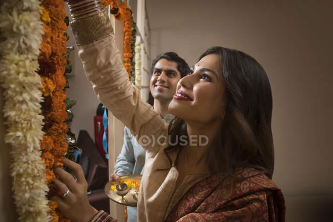 Ritratto di giovane coppia adulta in abito tradizionale decorazione casa con fiori — Foto stock