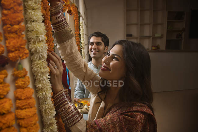 Portrait of young adult couple in traditional dress decorating home with flowers — Stock Photo