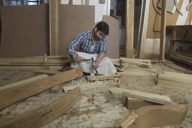 Карпентер робота з зубилом і молотком на підлозі в майстерні — стокове фото