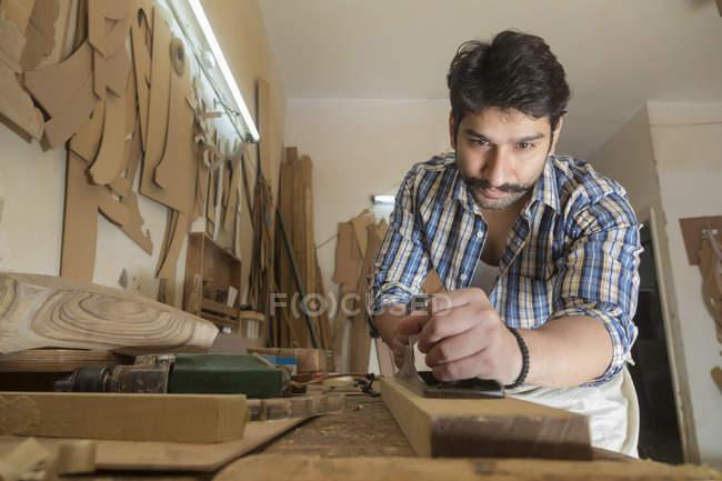 Inquadratura dal basso del carpentiere che lavora in officina — Foto stock