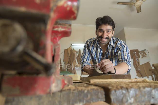 Inquadratura dal basso di Smiling carpentiere che lavora in officina — Foto stock