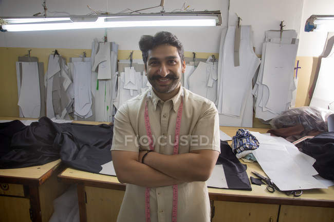 Smiling tailor standing with arms crossed in workshop — Stock Photo