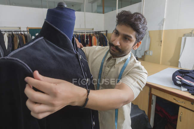 Портной, надевая манекен в мастерской, чтобы проверить установку полу сшитые пальто — стоковое фото