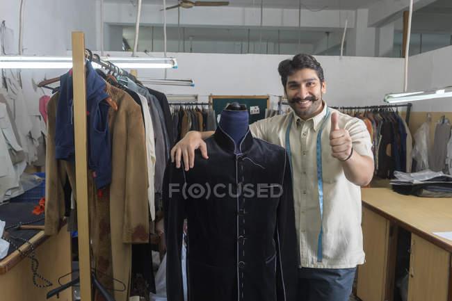 Alfaiate em pé ao lado do manequim usando casaco semi-costurado na oficina — Fotografia de Stock