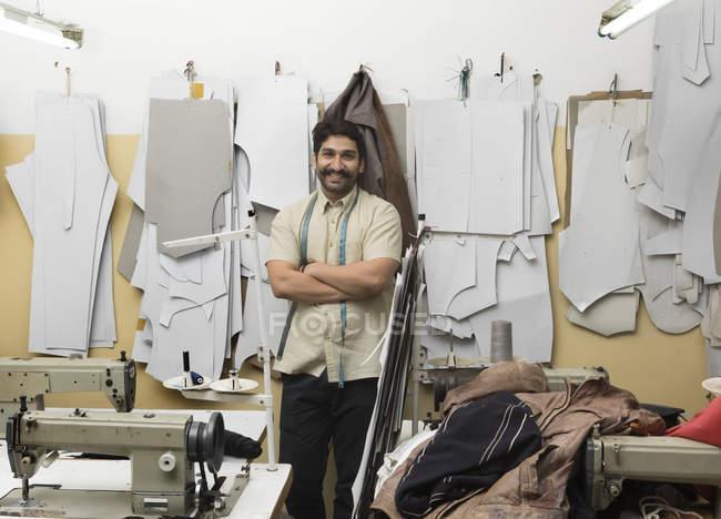 Lächelnder Schneider mit verschränkten Armen in Nähmaschinenwerkstatt — Stockfoto