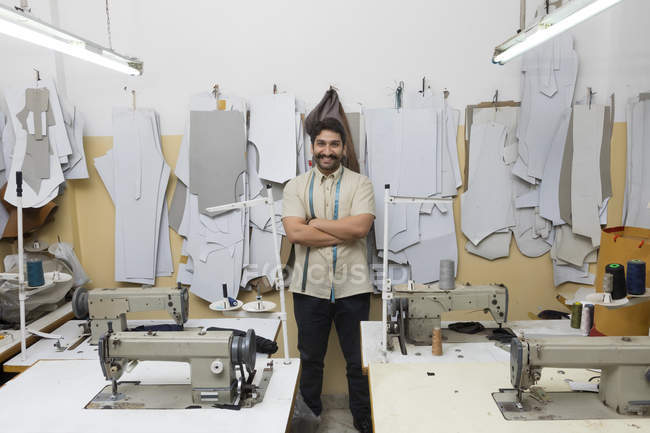 Smiling tailor standing with arms crossed in workshop with sewing machines — Stock Photo