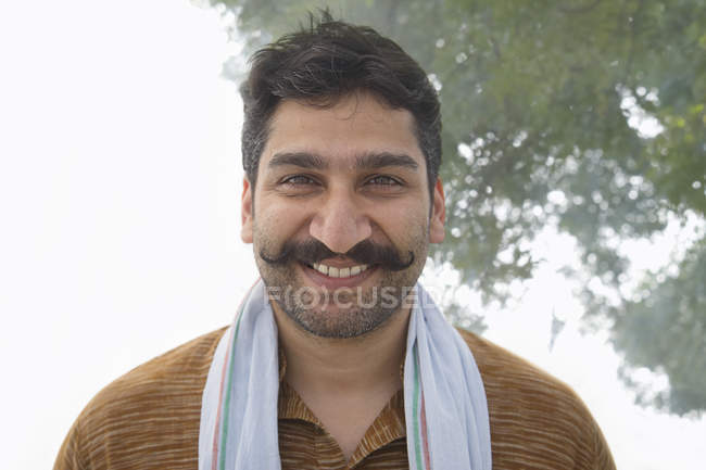 Portrait of Indian smiling village man with curled mustache — Stock Photo