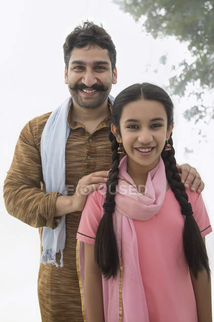 Portrait of smiling Indian man and girl looking at camera — Stock Photo