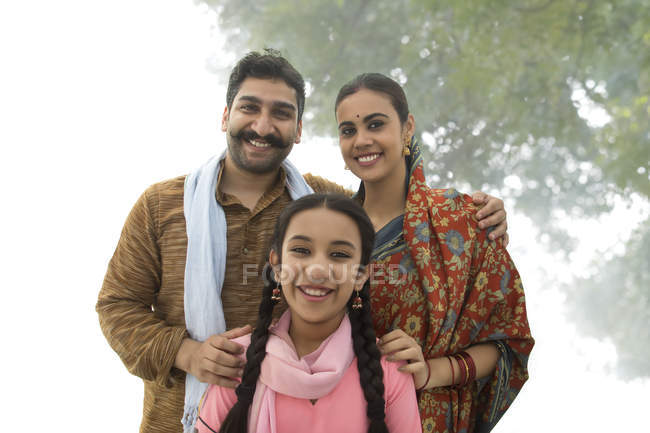 Portrait of smiling Indian family looking at camera outdoors — Stock Photo