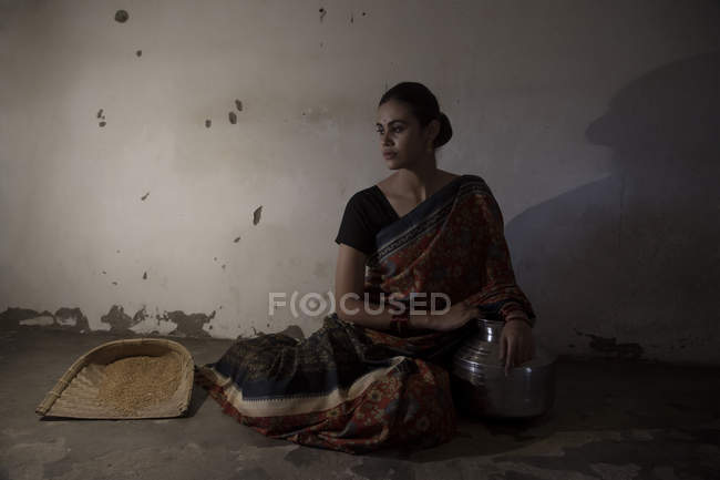 Indian woman sitting on floor in dimly lit room — Stock Photo