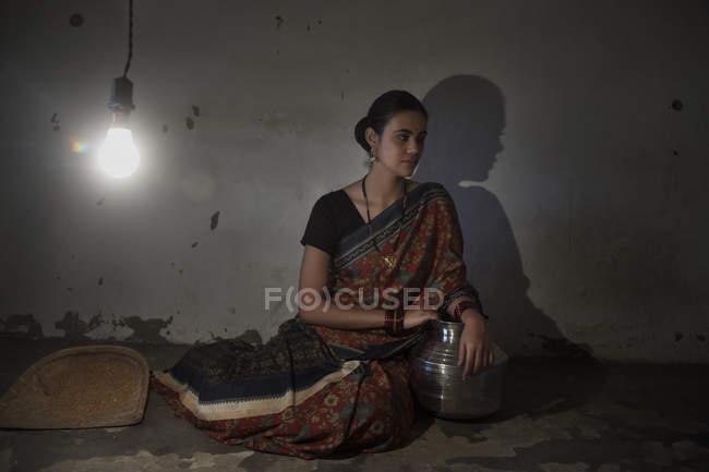 Mujer India sentada en el piso en la habitación débilmente iluminada - foto de stock