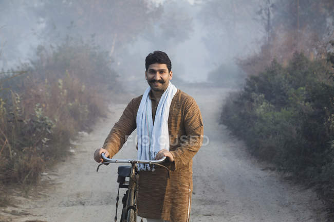Male farmer on country-road holding bicycle and looking at camera — Stock Photo