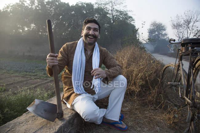 Lächelnde Landwirt Landwirtschaft Nahfeld sitzen und halten Spaten — Stockfoto
