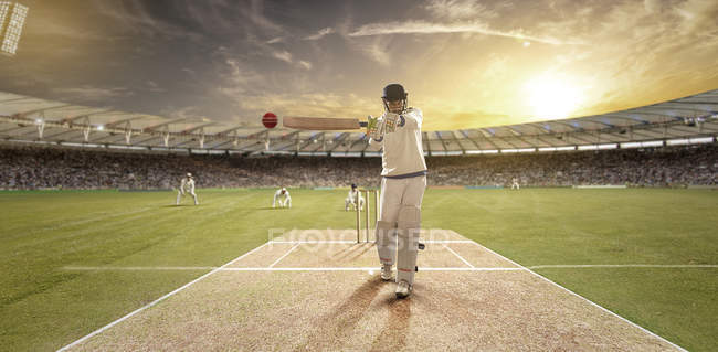 Young sportsman hitting ball while batting at cricket field, selective focus — стокове фото