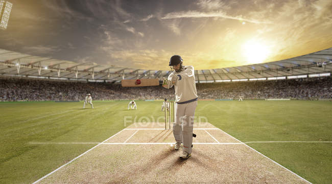 Young sportsman striking ball while batting at cricket field — стокове фото