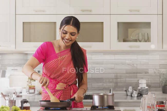 Woman in saree cooking in the kitchen — Stock Photo