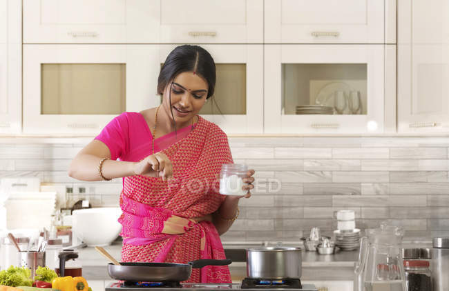 Woman sprinkling salt in the dish — Stock Photo