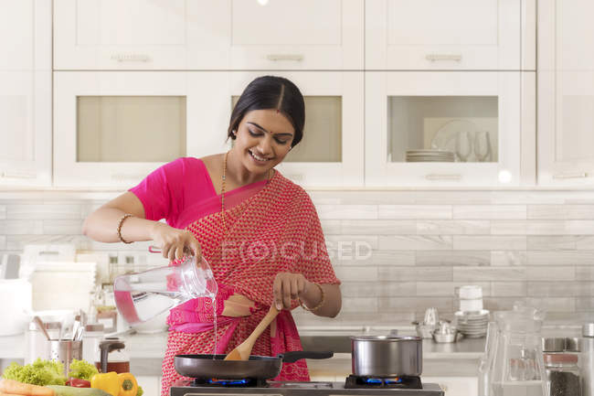 Жінка поливає воду в сковороді. — стокове фото