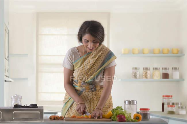Женщина, измельчения овощи в кухне — стоковое фото