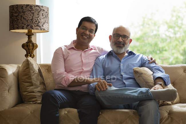Père et fils assis ensemble à la maison — Photo de stock