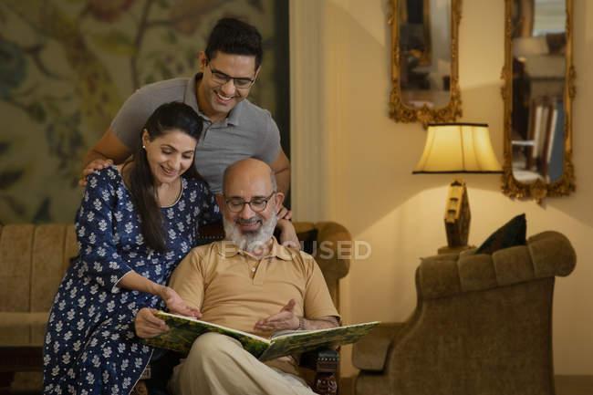 Vater, Mutter und Sohn schauen auf ein Buch und lächeln. (Familie) — Stockfoto