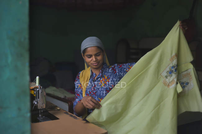 Young girl holding a cloth while stitching — Stock Photo