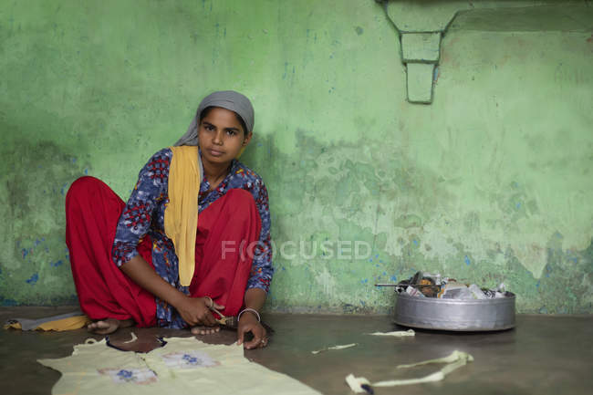 Young girl cutting the cloth for stitching — Stock Photo