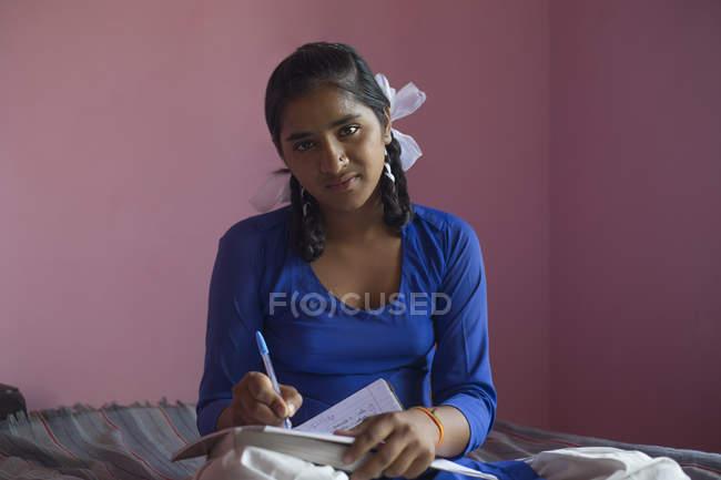 Scuola ragazza scrivendo nel suo taccuino — Foto stock