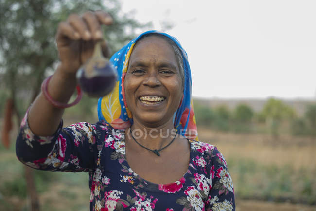 Woman holding brinjal and smiling, in the field — Stock Photo