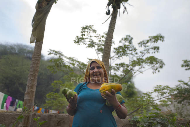 Woman holding fruits and smiling — Stock Photo