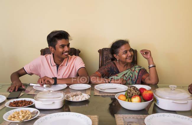 Jeune garçon sourit avec sa grand-mère sur la table à manger à la maison . — Photo de stock