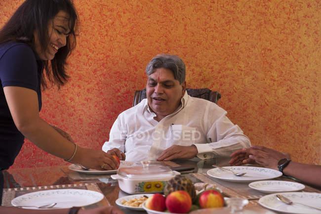 Belle-fille servant son père sur la table à manger à la maison . — Photo de stock