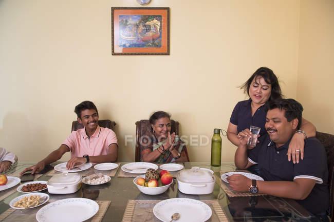 Joyeux famille assis autour de la table à manger à la maison . — Photo de stock