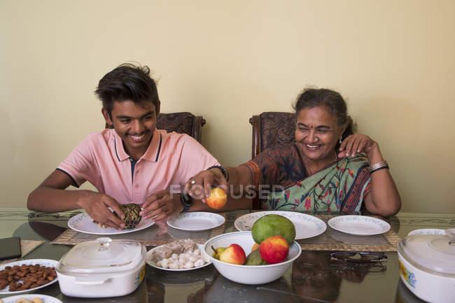 Grand-mère servant son petit-fils sur la table à manger à la maison . — Photo de stock