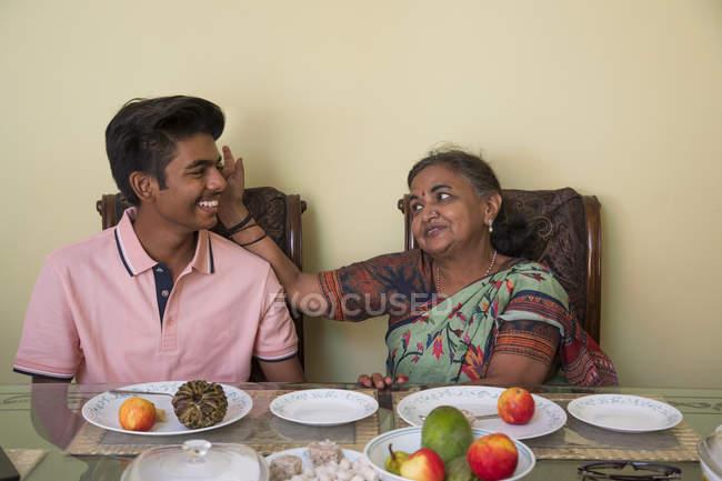 Grand-mère bénissant son petit-fils sur la table à manger à la maison . — Photo de stock