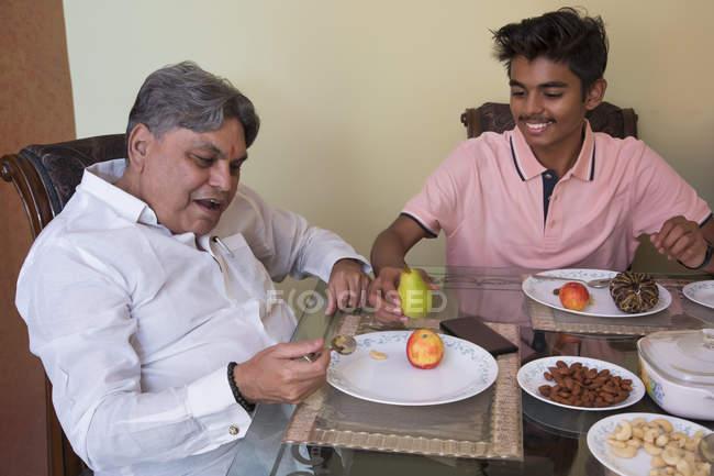 Petit-fils servant son grand-père sur la table à manger à la maison . — Photo de stock