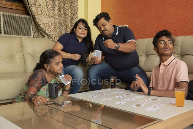 Joyeux jeu de famille avec des cartes dans le salon à la maison . — Photo de stock