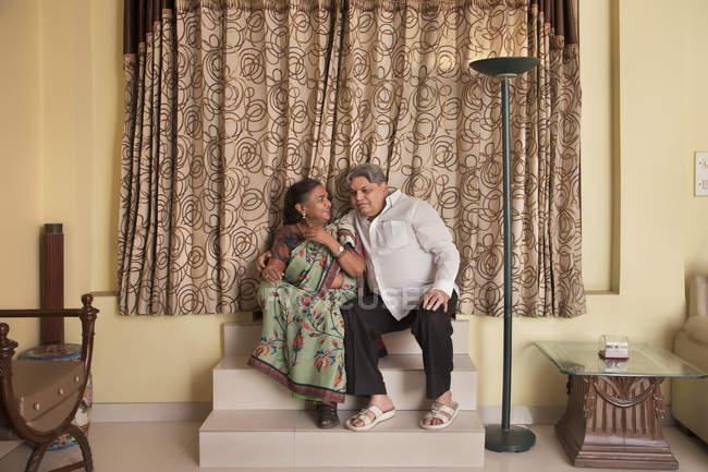 Couple âgé assis dans les escaliers à la maison . — Photo de stock