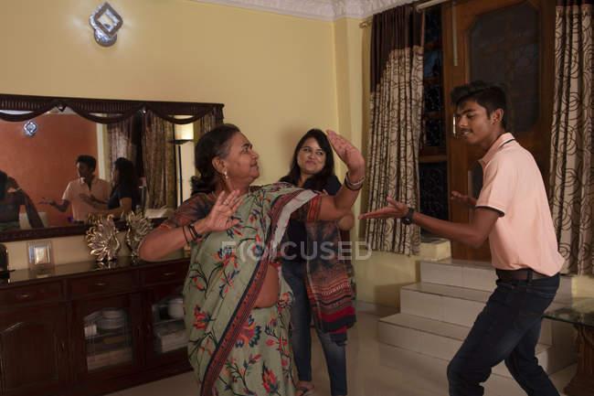 Fils dansant avec sa mère et sa grand-mère dans le salon à la maison . — Photo de stock