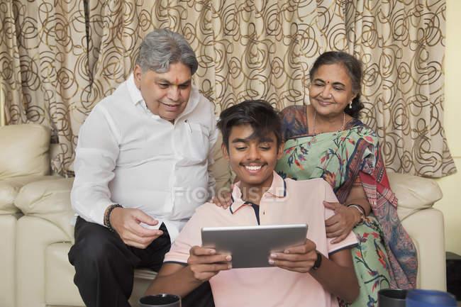 Enkel zeigt seinen Großeltern zu Hause im Wohnzimmer ein Tablet. — Stockfoto