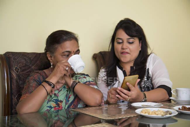Belle-fille montrant son téléphone à sa belle-mère à la maison . — Photo de stock