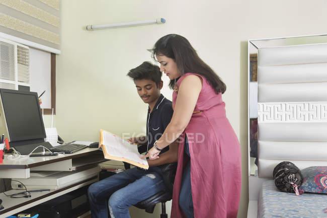Mutter hilft ihrem Sohn bei Examensvorbereitung zu Hause. — Stockfoto